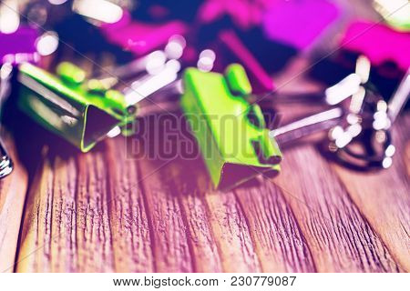 Colorful Paper Clip On Wooden Background. Green And Lila Paper Clip. Back To School And Office Work