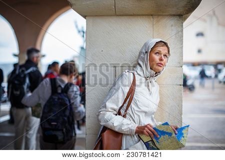Gorgeous female tourist with a map discovering a foreign city - waiting for the rain to stop.