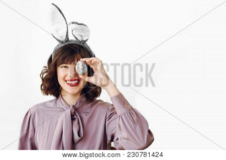 Happy Easter. Beautiful Stylish Girl In Bunny Ears Holding Colored Easter Egg On White Background Is