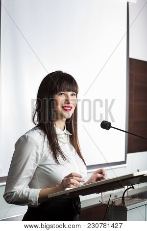 Pretty, young business woman giving a presentation in a conference/meeting setting.