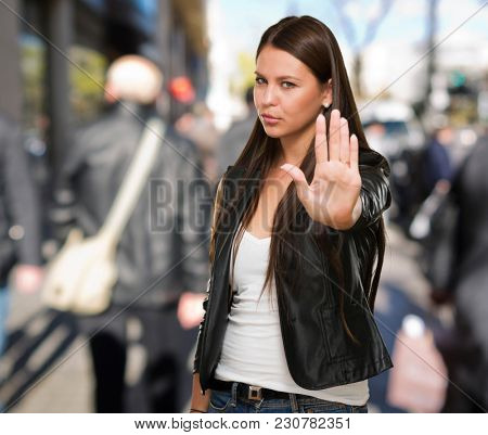 Young Woman Showing Stop Hand Gesture against a street background