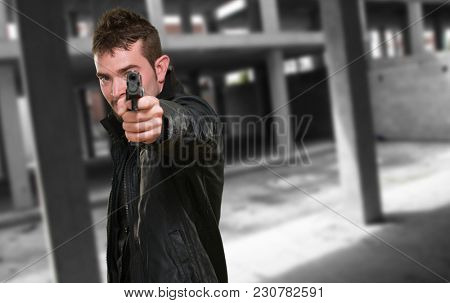 man with leather jacket pointing with gun, indoor