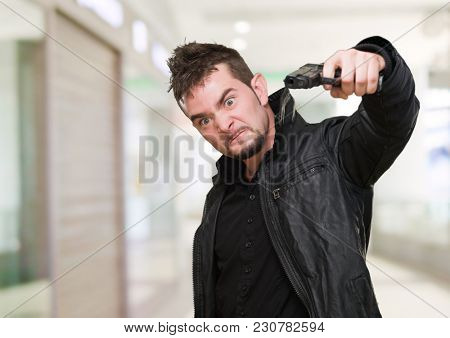 furious man pointing with a gun against an abstract background