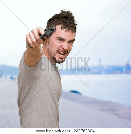 furious man pointing with gun at a port