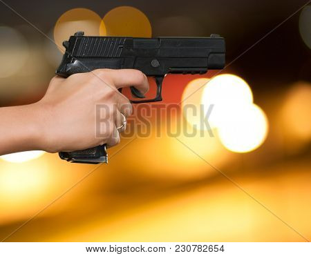 Woman's Hand With A Gun against a city by night