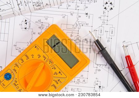 Electronics And Engineering. Printed Drawings Of Electrical Circuits And Digital Multimeter. Science