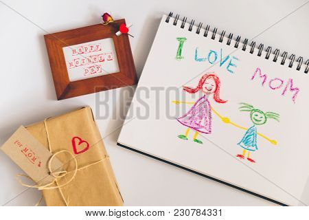 Happy Mother Day Text In Wooden Frame With Craft Gift Box And Child Picture On White Background