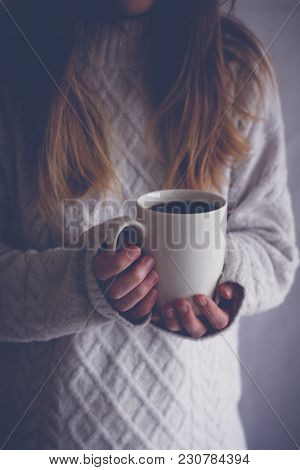 A Midsection Of A Blonde Haired Girl In A Cosy Sweater Holding Up A White Cup Indoors And In The Sha