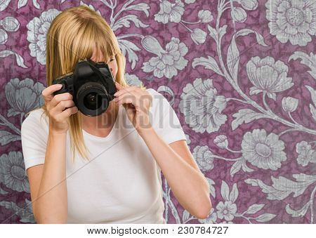 Young Woman Photographing against a floral vintage background