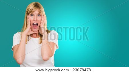 Portrait Of Shocked Woman against a blue background