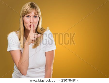 Woman With Finger On Lip against an orange background