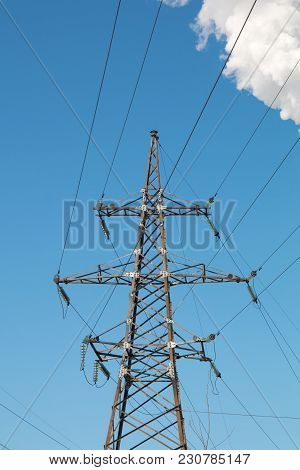 High Voltage Power Line Support On Blue Sky Background. Electricity Power Station