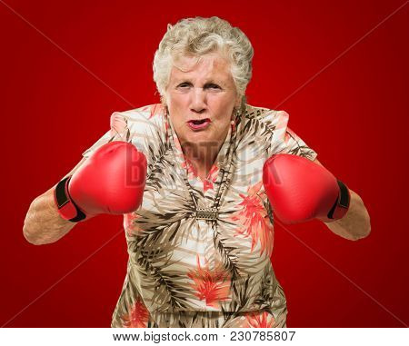 Angry Mature Woman Wearing Boxing Gloves On Red Background