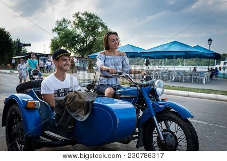 Funny Young Couple Is Traveling On A Retro Motorcycle. Beautiful Man With Girlfriend Went In Road Tr