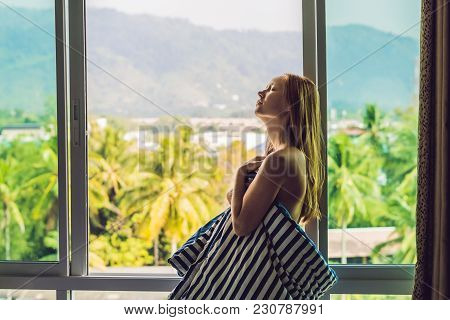 Young Happy Woman Woke Up In The Morning In The Bedroom By The Window With Beautiful Mountain Views.