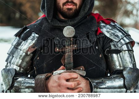 Bearded Man Knight In Iron Armor With A Sword