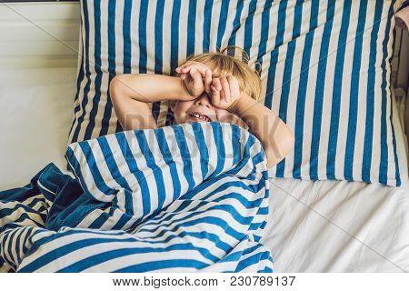 The Cute Boy Woke Up In His Bed. Children Sleep Concept.