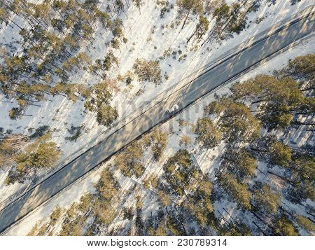 Snowy Road With A Moving Car In Winter. Aerial Photography