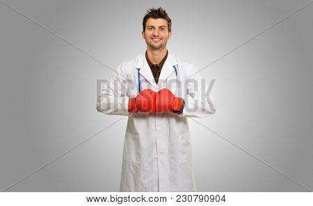 Young Doctor Wearing Boxing Gloves With Hands Together On Grey Background