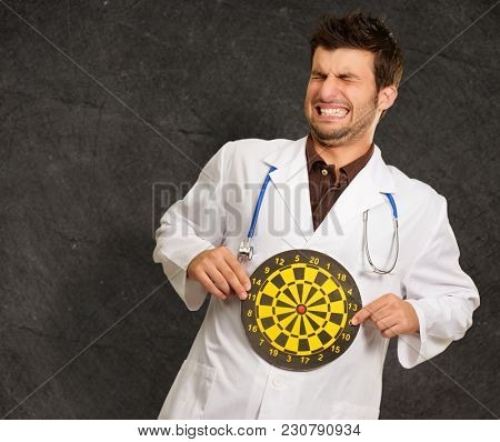Scared Young Doctor Holding Bulls Eye, Indoor