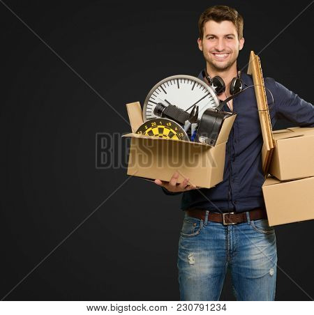 Happy Young Man Holding Cardboxes On Black Background