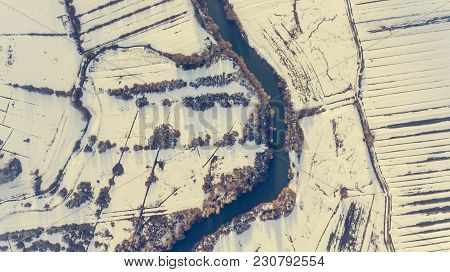 Aerial View Riverbend Passing Snow Covered Fields. Drop Down Photography.