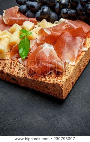 Italian Food With Grapes, Prosciutto And Cheese On Cork Cutting Board. Dark Concrete Background