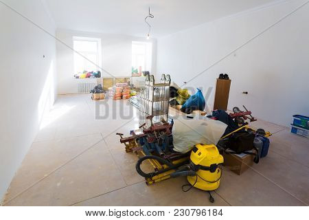 Construction Materials And Tools In The Room With Painted Walls And Ceiling Of Apartment Is Under Co