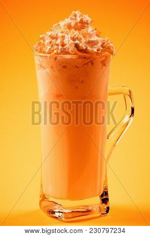 The Orange Frothy Drink With Whipped Cream Is On Yellow Background. Smoothie Or Milkshake.