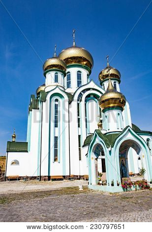 White church with gold domes a part of the European architecture. Russian orthodox church with typical golden onion domes