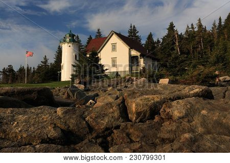 The Picturesque Little River Lighthouse, Near Cutler, Maine Sets Above The Rocky Coastline. The Scen