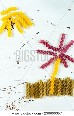 Various Kinds Of Colored Raw Pasta On A White Background, Top View, In The Form Of Flower Fields And