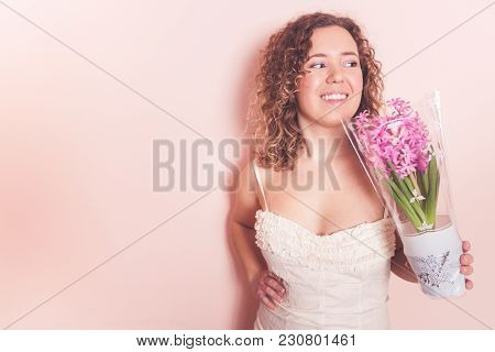 Beautiful curly woman in white dress with hyacinth flowers in hands on a light pink background. Hell