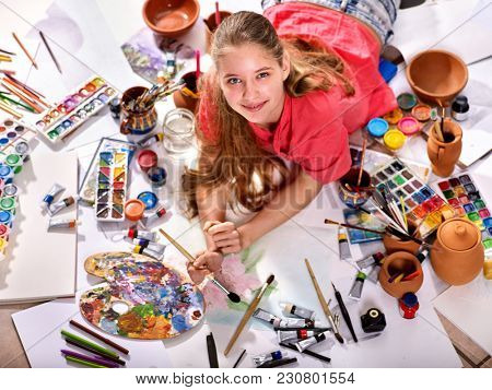 Authentic artist children girl paints with set palette watercolor paints palette and brush in morning sunlight. Painting in studio on floor. reparation for exam in drawing.