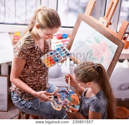 Artist painting easel in studio. Authentic children girl paints with set palette watercolor paints palette and brush in morning sunlight . Top view school indoor handmade crafts with window .