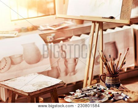 Authentic paint brushes still life on table in art class school as drawing course. Group of brush in clay jar. Quiet environment for creativity. Sale of artistic goods.