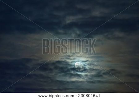 Moon In A Cloudy Sky. Night, Slightly Cloudy Sky. The Clouds Are Arranged In Parallel Layers. Behind