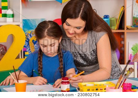 Child and teacher painting finger on easel. Girl and mother learn paint in class school. Child picture on background. Student draw a rainbow. Art children's school.
