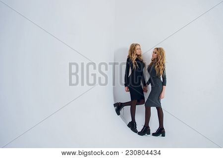 Two Beautiful Women In Black Night Fashion Dress Posing Isolated On A White Gray Background. Pretty