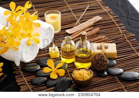 Spa setting with yellow orchid ,stones ,candle ,towel bowl on mat