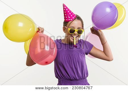 Cheerful Teenage Girl 12, 13 Years Old, With Balloons, In Festive Hat, Blowing A Pipe On White Backg