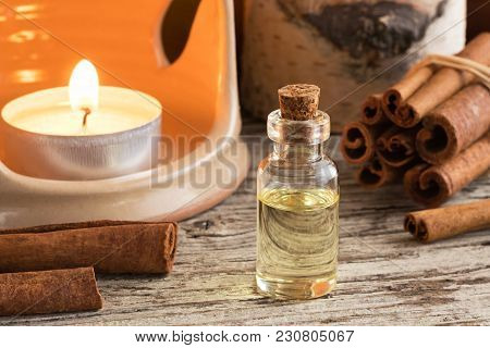 A Bottle Of Cinnamon Essential Oil With Cinnamon Sticks And An Aroma Lamp On A Table