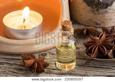 A Transparent Bottle Of Star Anise Essential Oil With Star Anise And An Aroma Lamp