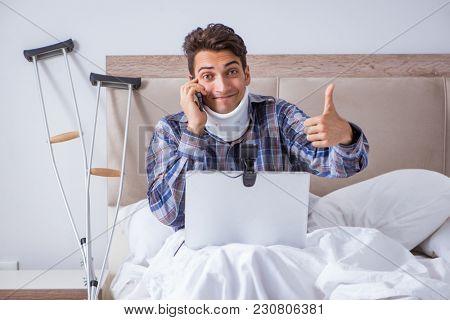 Injured man chatting online via webcam in bed at home