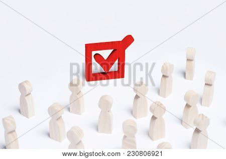 A Crowd Of People Looks At The Red Tick In The Box. The Concept Of The Political Process And Democra