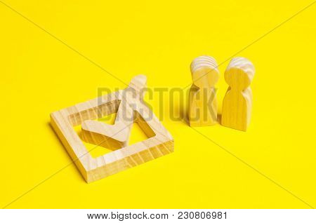 A Couple Is Looking At A Large Wooden Teak In A Box With A Yellow Background. The Concept Of The Pol
