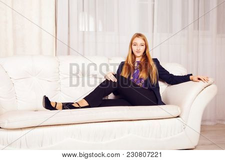 Beautiful blonde sitting on white sofa