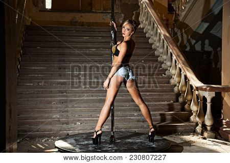 Beautiful brunette dancing on a pole on underground background