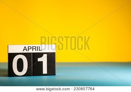 April 1st. Day 1 Of April Month, Calendar On Table With Yellow Background. Spring Time, Empty Space