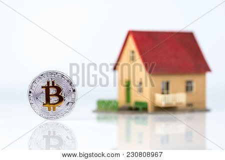 Bitcoin And Private House Model At Light Background. Real Estate Theme. Concept Of Buying A Property